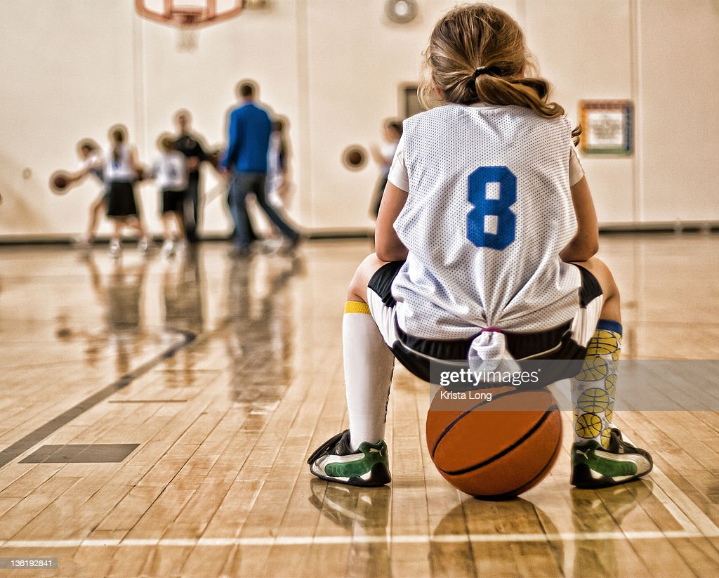 Girl sitting on basketball : Stock Photo