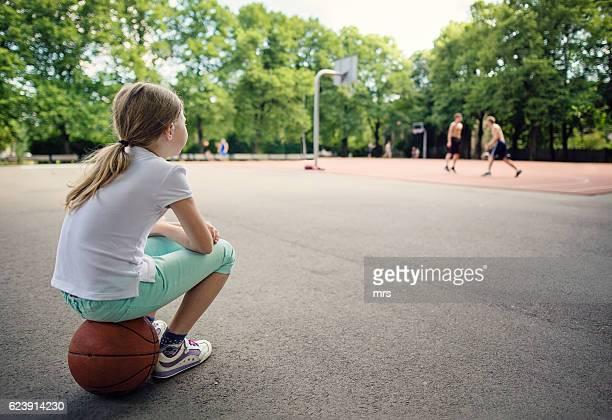 Girl sitting on basketball, waiting to play