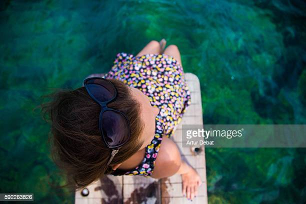 Girl sitting on beach dock with feet on water contemplating the Mediterranean Sea Costa Brava on summer with overhead view.