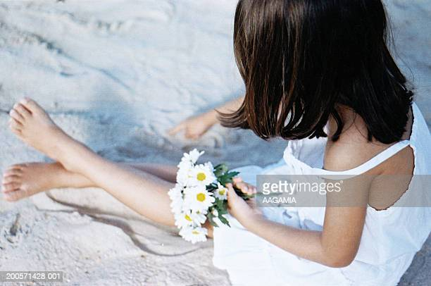 Girl (8-9) sitting on beach holding flower, elevated view