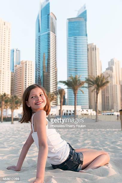 Girl sitting on beach, smiling over shoulder