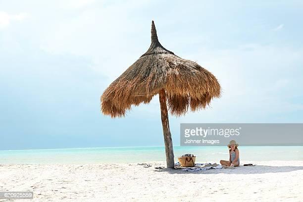 Girl sitting on beach under thatched umbrella