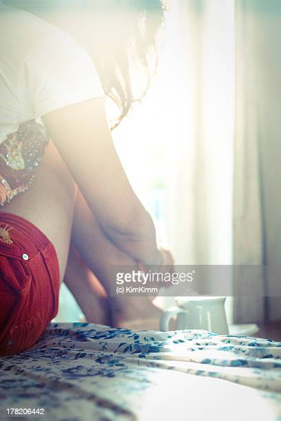 Girl sitting on bed and cup of tea in the morning