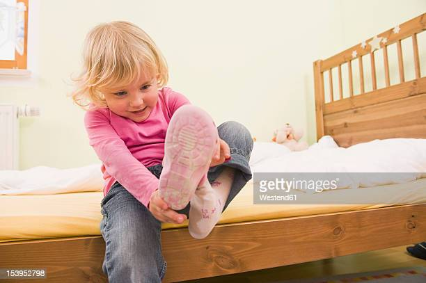 Girl sitting on bed and putting shoes