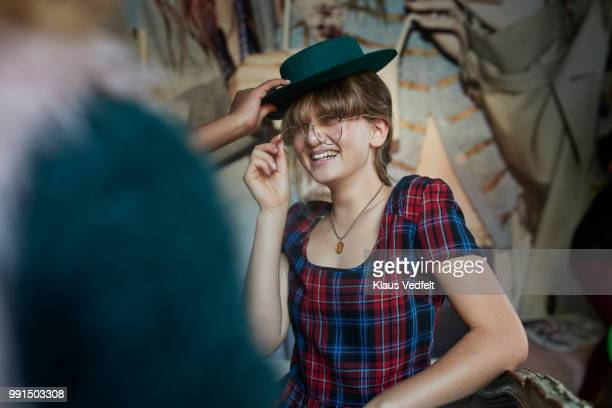 girl sitting on bed and trying hat and glasses with friends - imperfection stock pictures, royalty-free photos & images