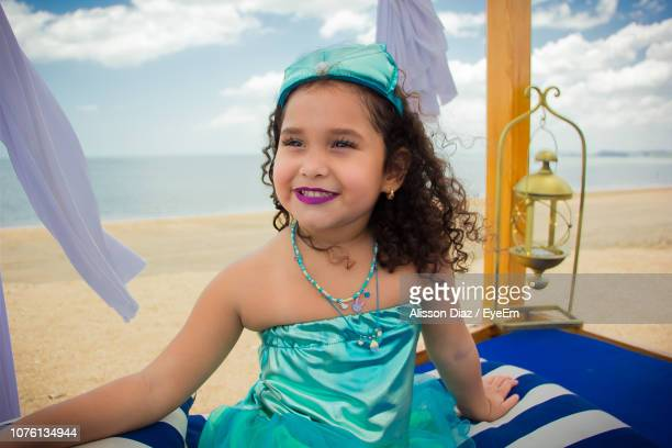 girl sitting on bed at beach against sky - alisson stock pictures, royalty-free photos & images
