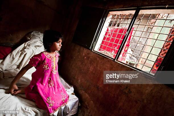 girl sitting on bed - bangladesh stockfoto's en -beelden