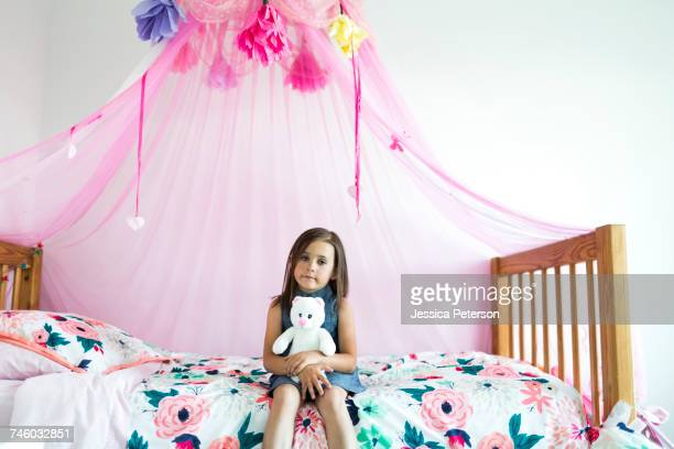Girl (6-7) sitting on bed