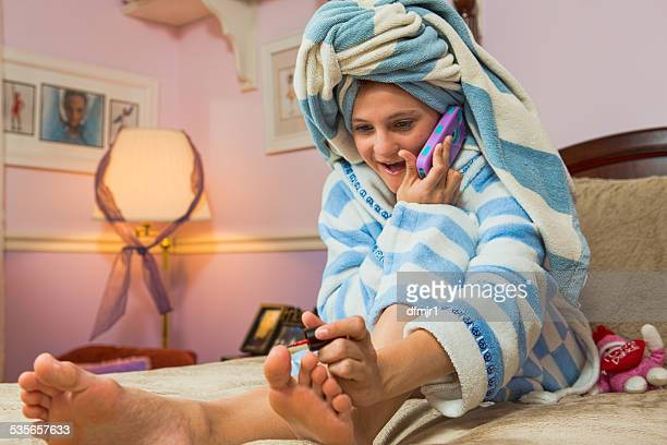 girl sitting on bed  talking on mobile phone while painting toenails - teen girls toes stock photos and pictures