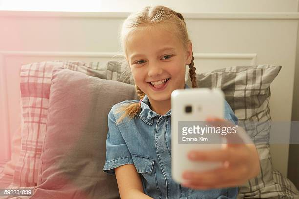 Girl sitting on bed using smartphone to take selfie smiling