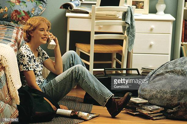 Girl sitting on bedroom floor and talking on telephone