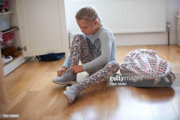 Girl sitting on bedroom floor tying booty laces