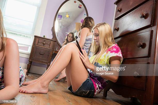 girl sitting on bedroom floor with digital tablet - barefoot girl stock photos and pictures