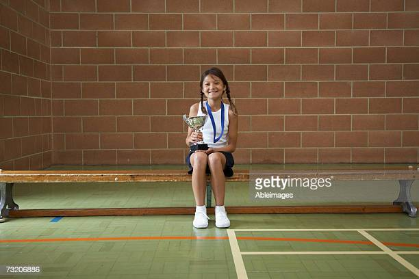 girl (10-12) sitting on bench in gym, with trophy - 10 11 anni foto e immagini stock
