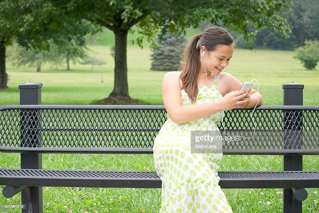 Girl sitting on bench listening to music : Stock Photo