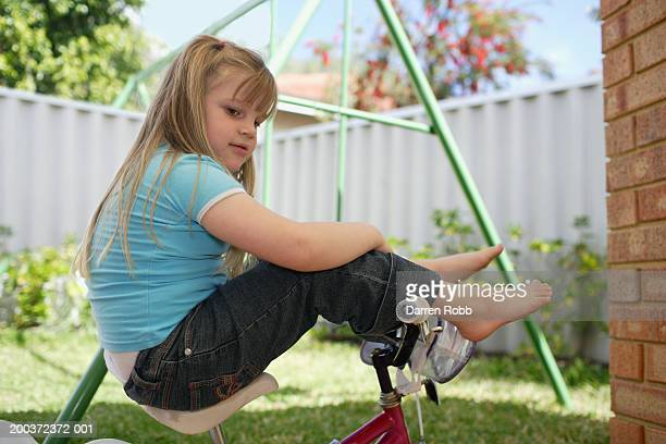 Girl (4-6) sitting on bicycle outdoors