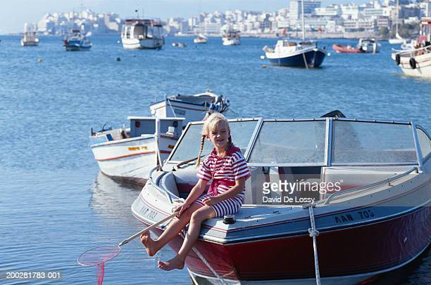 girl (6-7) sitting on bow of boat - bang boat stock pictures, royalty-free photos & images