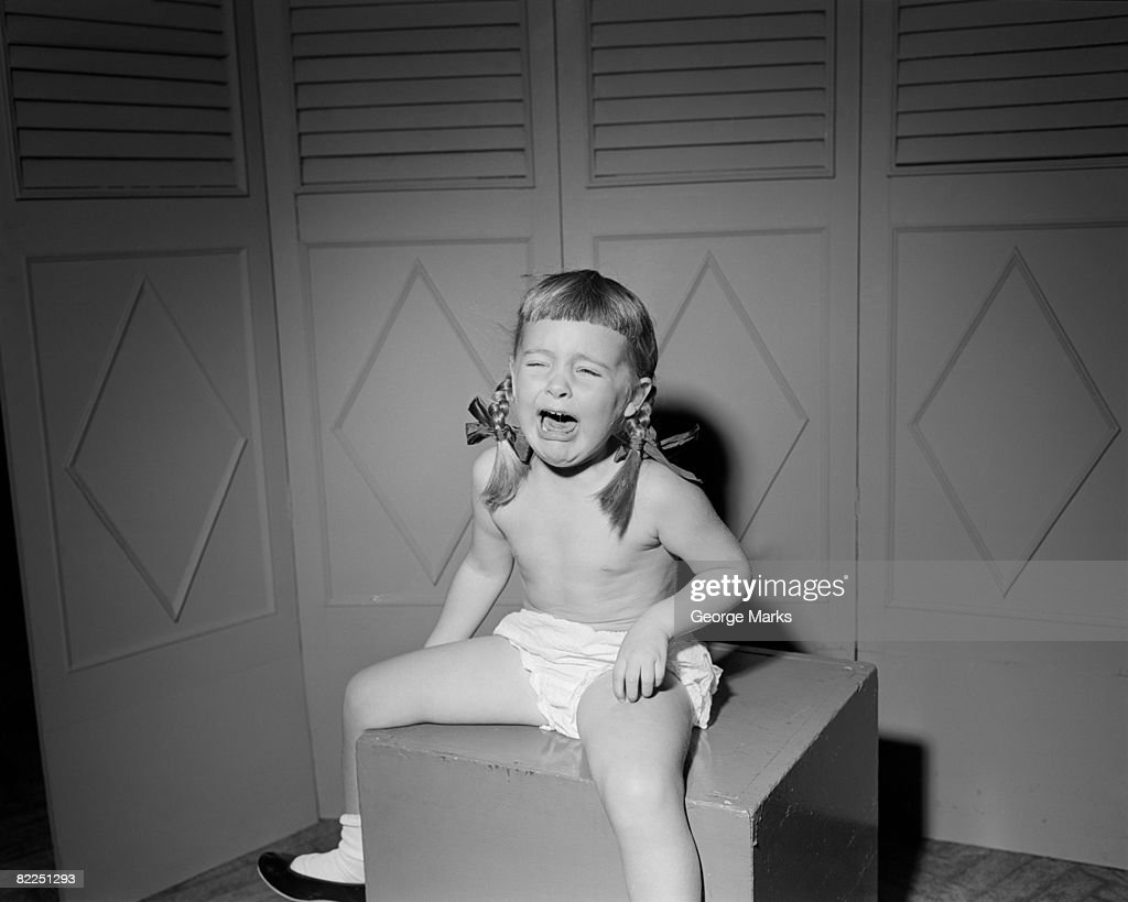 Girl (6-7) sitting on box and crying : Stock Photo