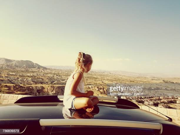 Girl Sitting On Car Roof By Landscape Against Sky