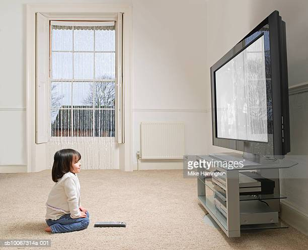 Girl (2-3 years) sitting on carpet, watching tv, side view