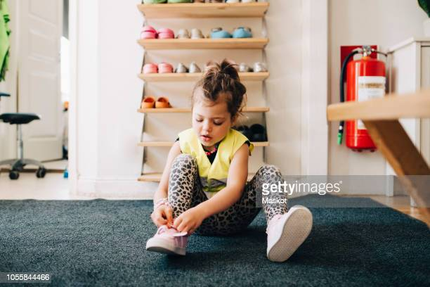 girl sitting on carpet wearing shoes against rack in cloakroom at child care - girl shoes stock pictures, royalty-free photos & images
