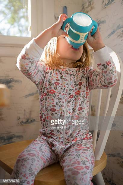 Girl (2-3) sitting on chair and drinking milk from sippy cup