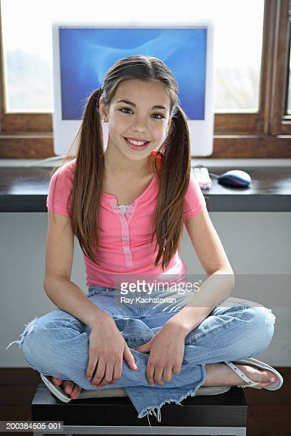 Girl (10-12) sitting on chair, computer in background