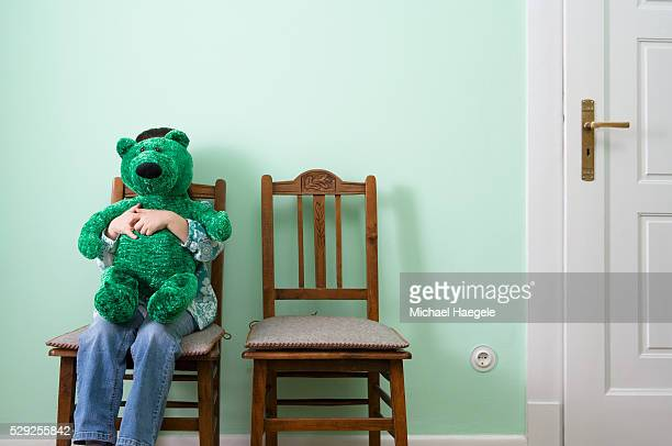 Girl Sitting on Chair Holding Teddy Bear in Front of Her