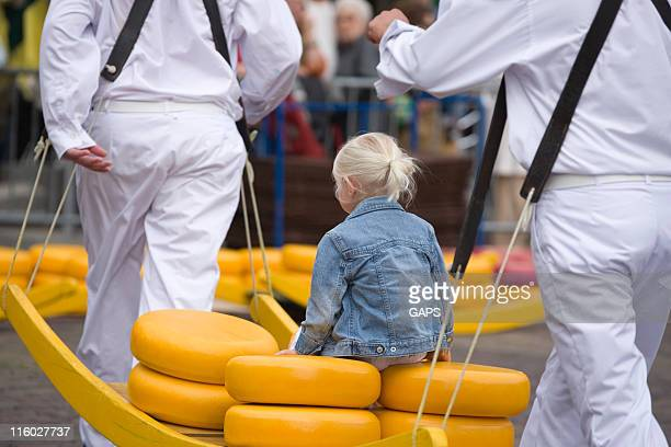girl sitting on cheeses and carried by special craftsmen - north holland stock pictures, royalty-free photos & images