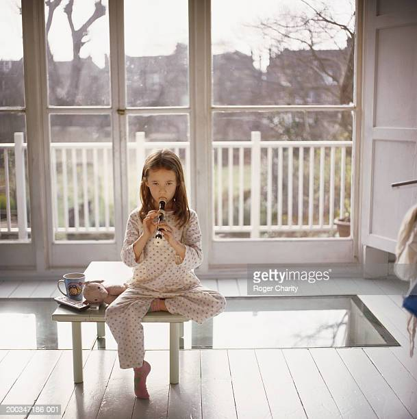 Girl (6-8) sitting on coffee table practicing with recorder