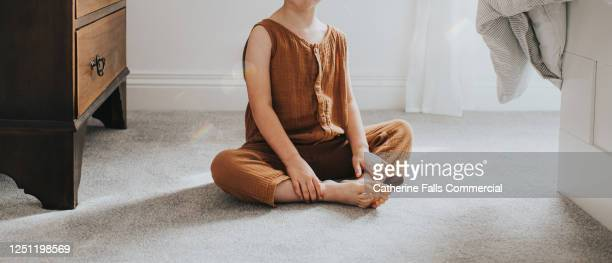 girl sitting on comfortable thick grey carpet in a sunny room - barefoot stock pictures, royalty-free photos & images