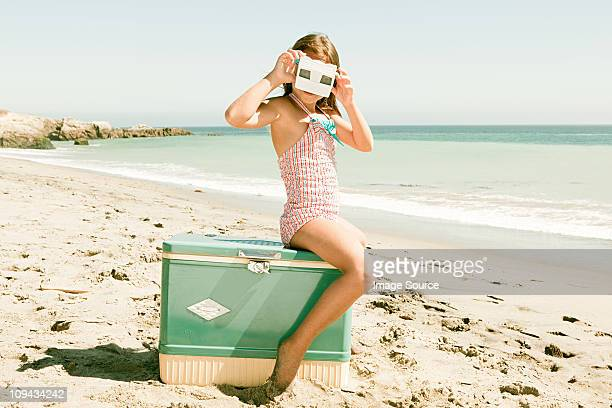 Girl sitting on coolbox on beach looking through slide viewer