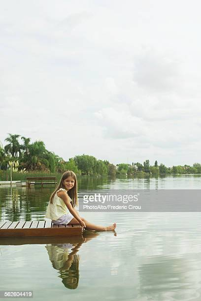 Girl sitting on dock with feet dangling in lake, portrait