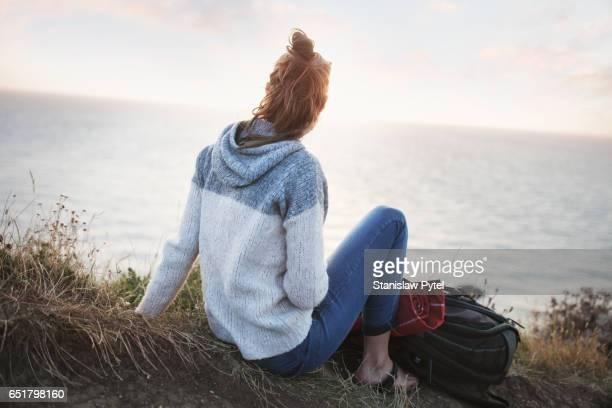Girl sitting on edge of grassy cliff