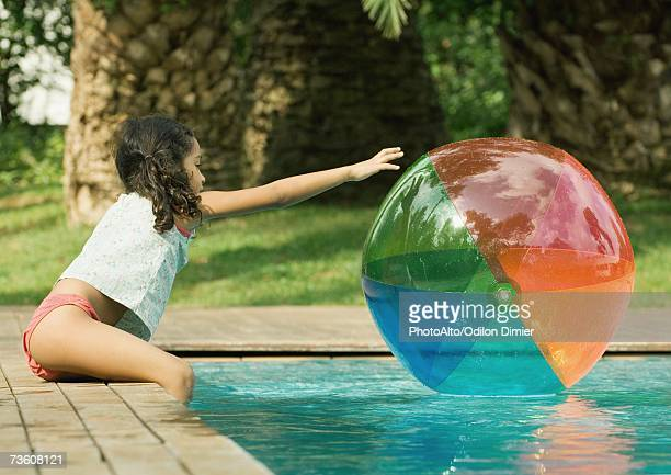 girl sitting on edge of pool, reaching for beach ball in water - bending over stock pictures, royalty-free photos & images