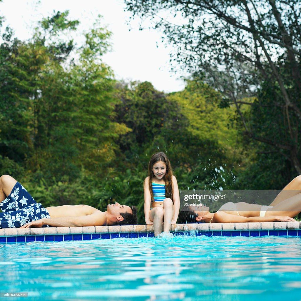 Swimming Pool Edge: Girl Sitting On Edge Of Swimmingpool Kicking Water While