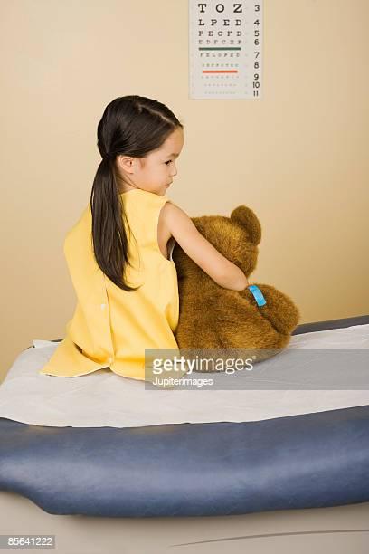 Girl sitting on exam table with teddy bear