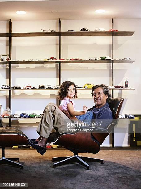 Girl (3-5) sitting on father's lap, collection of model cars on shelf