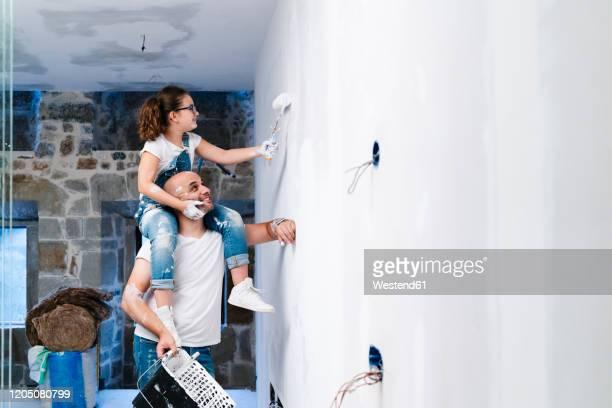 girl sitting on father's shoulders painting the wall of her new house - heimwerken stock-fotos und bilder