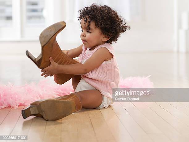 Girl (2-3) sitting on floor at home, trying on adult-sized high-heeled boots, side view