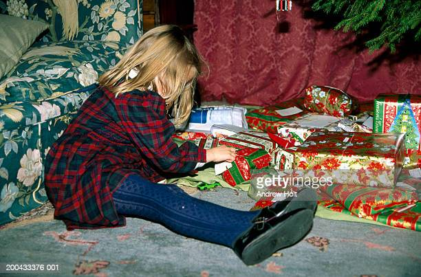 girl (4-6 years) sitting on floor by christmas tree looking at label on present - little girls dressed up wearing pantyhose stock photos and pictures
