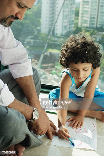 Girl sitting on floor drawing with crayons and paper, father next to her