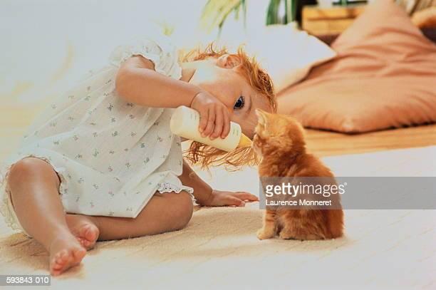 Girl (1-3) sitting on floor, feeding kitten with baby bottle