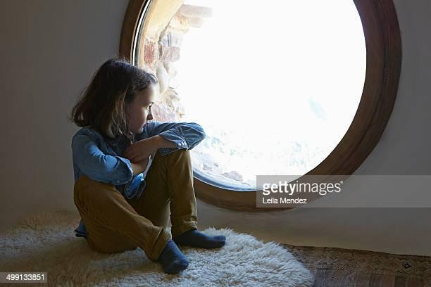 Girl sitting on floor gazing through circular window