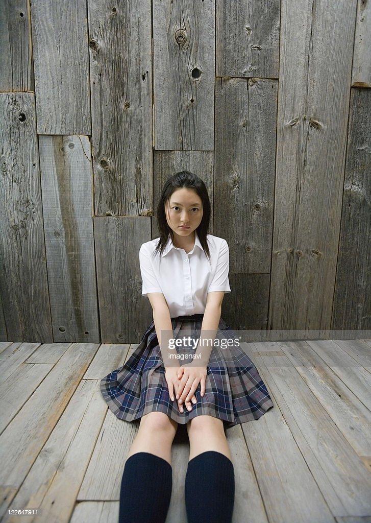 Girl sitting on floor in school uniform : Stock Photo