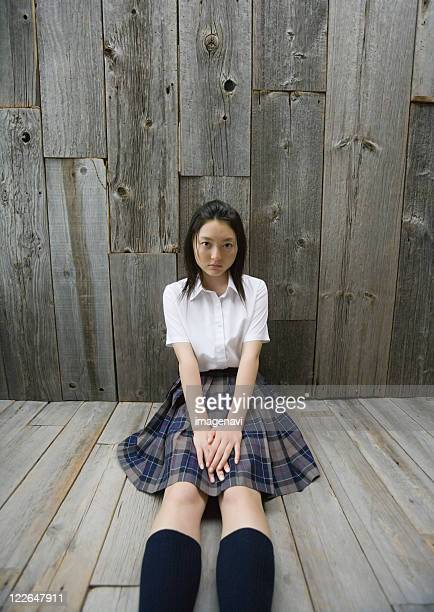 Girl sitting on floor in school uniform