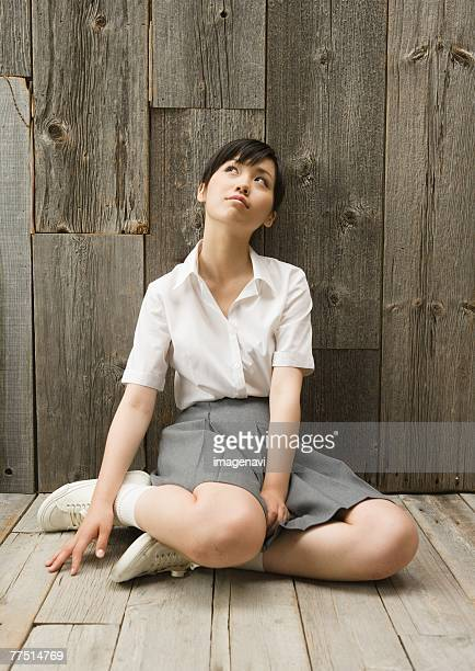 girl sitting on floor in school uniform - japanese short skirts stock photos and pictures