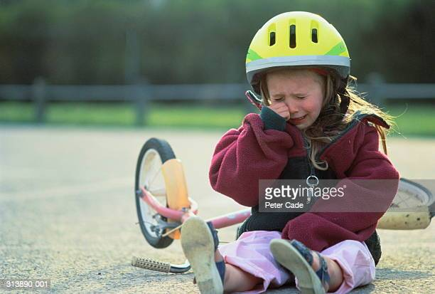 Girl (4-6) sitting on floor next to bicycle crying