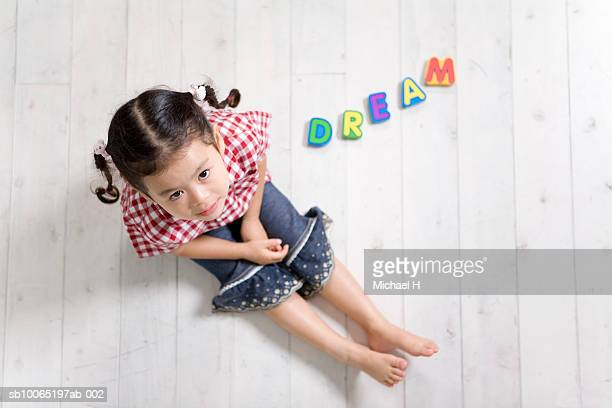 Girl (4-5) sitting on floor next to letters reading 'dream', portrait, overhead view