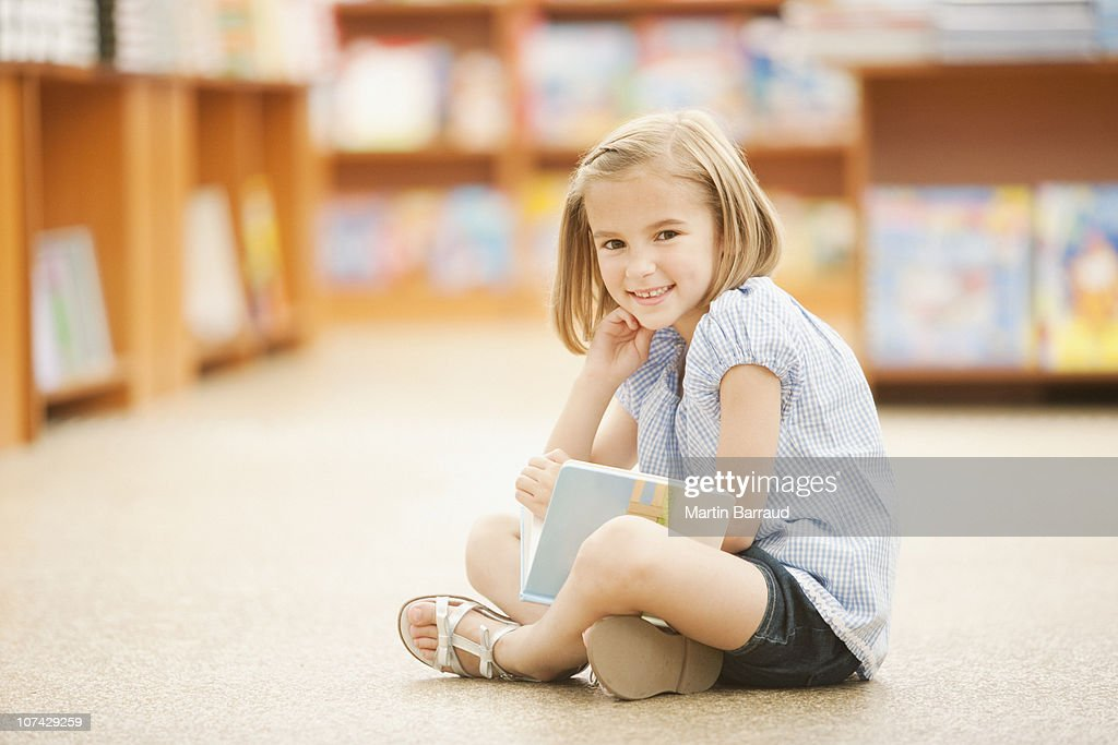 Girl sitting on floor of library with book : Stock Photo